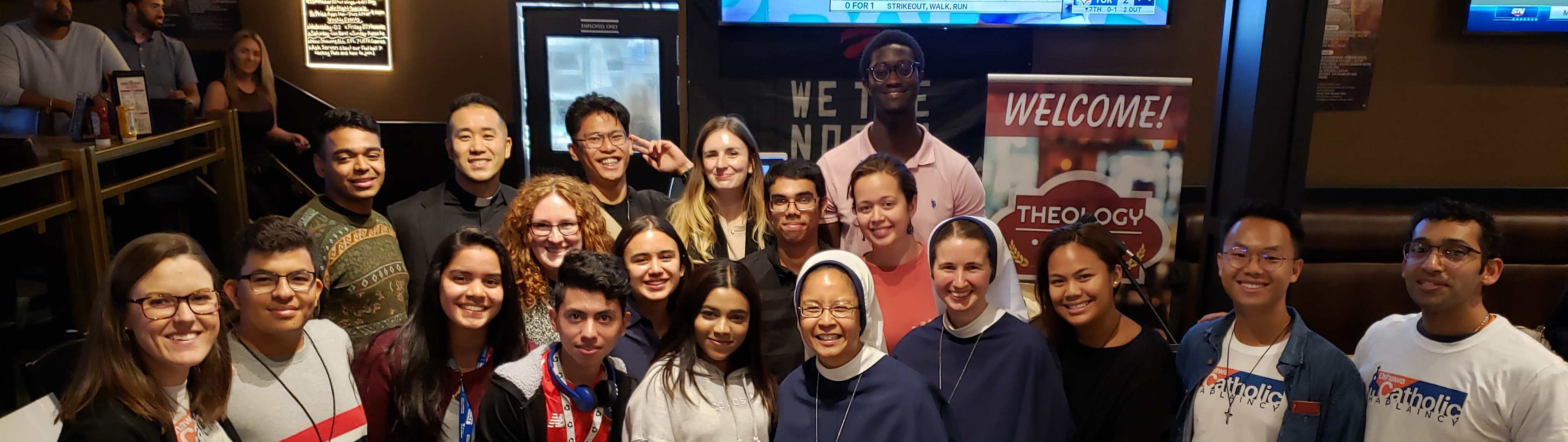 Group of male and female young adults with a few nuns gathered inside a pub/restaurant smiling for a photo